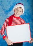 Jeune garçon dans le chapeau rouge de Santa tenant le conseil blanc Images stock
