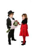Jeune garçon dans le smoking donnant des roses de fille Images stock