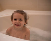 Jeune garçon dans un bain moussant Image stock
