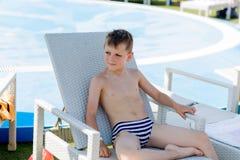 Jeune garçon dans un maillot de bain sur une étagère par la piscine Photo stock