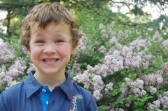 Jeune garçon de sourire avec le backgroun floral Photographie stock libre de droits