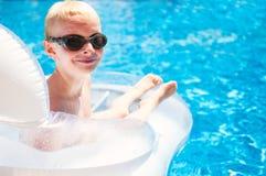 Jeune garçon de sourire s'étendant sur un matelas de flottement dans un PO de natation Photographie stock