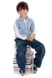 Jeune garçon de sourire s'asseyant au-dessus de la pile des livres Images libres de droits