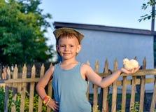 Jeune garçon de sourire tenant un poussin jaune pelucheux Images stock