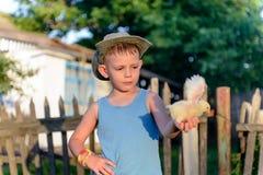 Jeune garçon de sourire tenant un poussin jaune pelucheux Photos stock