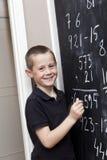 Jeune garçon devant le tableau noir Images libres de droits