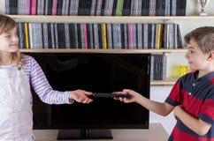 Jeune garçon donnant l'à télécommande à sa soeur devant le Th Photo stock