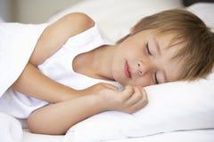 Jeune garçon dormant dans le lit Photos stock