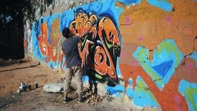 Jeune garçon doué beau faisant un graffiti coloré avec le jet d'aérosol sur le mur urbain de rue Lent modifié la tonalité cinémat clips vidéos