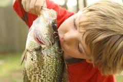 Jeune garçon embrassant des poissons qu'il a pêchés Photographie stock libre de droits