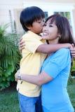 Jeune garçon embrassant la mère Photographie stock libre de droits