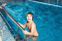 Jeune garçon employant l'échelle pour sortir la piscine photo stock