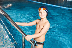 Jeune garçon employant l'échelle pour sortir la piscine Photographie stock