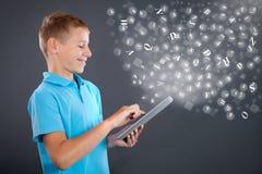 Jeune garçon employant le comprimé, l'étude d'école ou le concept de technologie Photo stock
