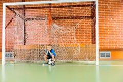 Jeune garçon ennuyé attendant sur une cour de football en salle Photo libre de droits