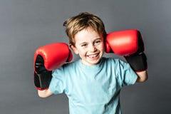 Jeune garçon enthousiasmé riant nerveusement avec des gants de boxe pour le combat Images stock