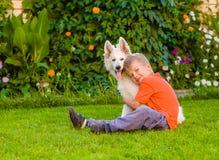 Jeune garçon et chiot suisse blanc du ` s de berger Photo libre de droits