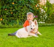 Jeune garçon et chiot suisse blanc du ` s de berger Image libre de droits