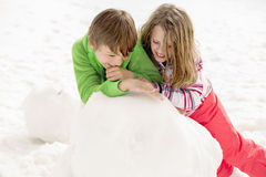Jeune garçon et fille construisant un bonhomme de neige Images libres de droits