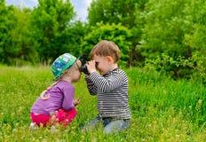 Jeune garçon et fille jouant avec des jumelles Photographie stock