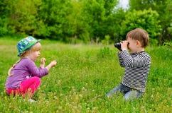 Jeune garçon et fille jouant avec des jumelles Image libre de droits