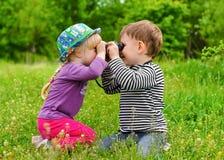 Jeune garçon et fille jouant avec des jumelles Photos libres de droits