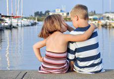 Jeune garçon et fille s'asseyant avant l'eau Photographie stock libre de droits