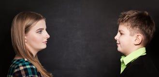 Jeune garçon et fille se regardant sur le fond de tableau noir Photos stock