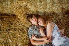 Jeune garçon et garçon et gyrl de lyingYoung de gil se situant en foin Portrait extérieur d'été de beaux couples en foin Portr ex Photographie stock