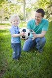 Jeune garçon et papa jouant avec du ballon de football en parc Photographie stock libre de droits