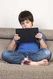 Jeune garçon et un comprimé numérique photos stock