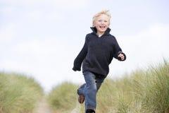 Jeune garçon exécutant sur la plage Photos libres de droits