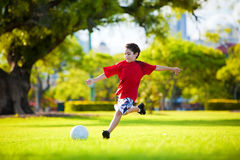 Jeune garçon excited donnant un coup de pied la bille dans l'herbe Photo stock