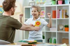 Jeune garçon expressif de sourire soulevant ses mains dans l'excitation images libres de droits