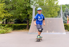 Jeune garçon faisant de la planche à roulettes au parc Image libre de droits