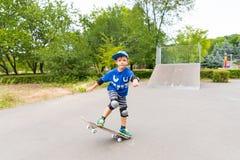 Jeune garçon faisant le tour simple sur la planche à roulettes Photographie stock libre de droits
