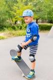 Jeune garçon faisant le tour simple sur la planche à roulettes Photo libre de droits