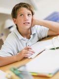 Jeune garçon faisant le travail dans sa chambre photographie stock libre de droits