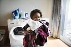 Jeune garçon faisant les travaux domestiques à la maison photo stock
