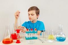 Jeune garçon futé faisant des expériences chimiques dans le laboratoire Photo libre de droits