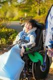 Jeune garçon handicapé dans le fauteuil roulant appréciant le parc dehors Photographie stock libre de droits