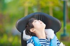 Jeune garçon handicapé dans le fauteuil roulant recherchant dans le ciel Photo libre de droits