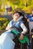 Jeune garçon handicapé dans le fauteuil roulant recherchant dans le ciel Photos libres de droits