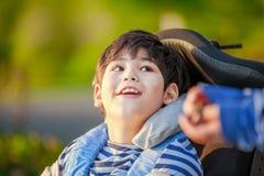 Jeune garçon handicapé dans le fauteuil roulant recherchant dans le ciel Photographie stock libre de droits