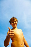 Jeune garçon heureux à la plage avec des pouces vers le haut Photographie stock