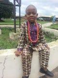 Jeune garçon heureux assis à une assemblée ouverte dans les beeds de port du Nigéria sur un vêtement traditionnel Image stock