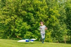 Jeune garçon heureux d'enfant jouant avec le cerf-volant lumineux en parc Photo libre de droits