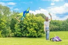 Jeune garçon heureux d'enfant jouant avec le cerf-volant lumineux en parc Images libres de droits