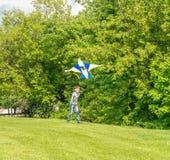 Jeune garçon heureux d'enfant jouant avec le cerf-volant lumineux en parc Photographie stock libre de droits