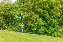 Jeune garçon heureux d'enfant jouant avec le cerf-volant lumineux en parc Photos libres de droits